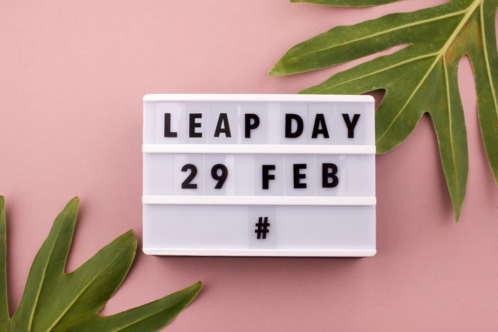 White Block Calendar Present Date 29 And Month February And Plant On Pink Background. Leap Day