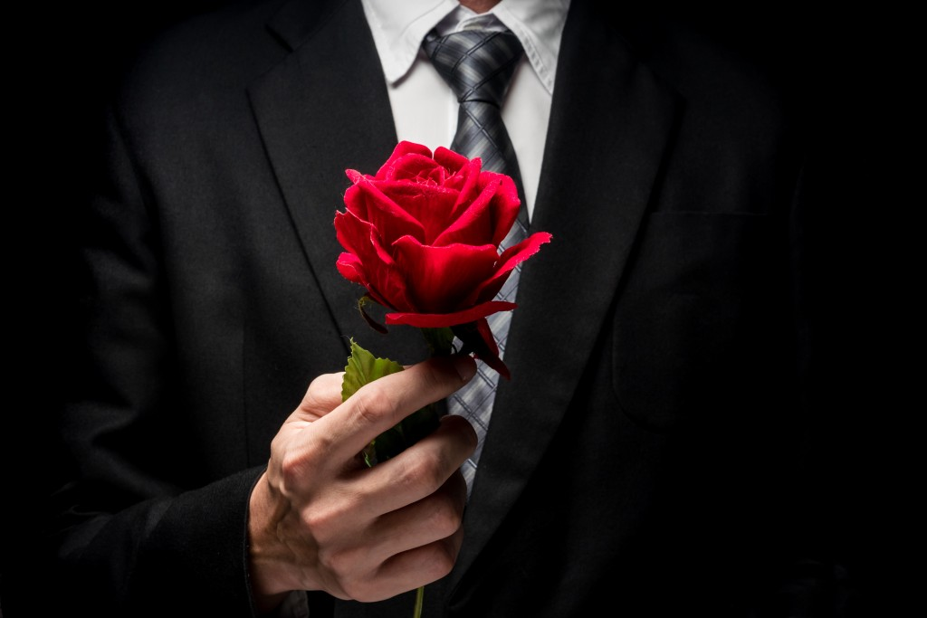 Close Up Of Man In Black Suit Holding Red Rose.