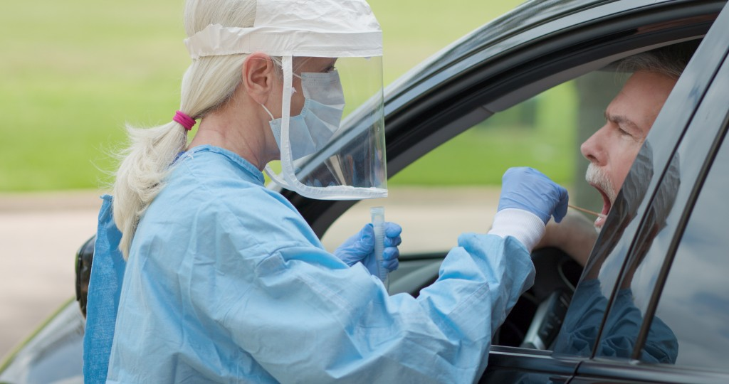 Dressed In Full Protective Gear A Healthcare Worker Collects A Sample From A Mature Man Sitting Inside His Car As Part Of The Operations Of A Coronavirus Mobile Testing Unit...