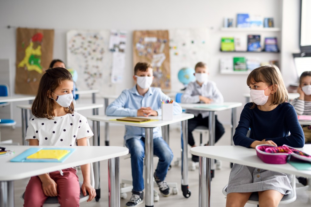 Children With Face Mask Back At School After Covid 19 Quarantine And Lockdown.