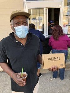 A neighbor grabs a box lunch to-go at Thelma's Kitchen. // Photo courtesy Thelma's Kitchen