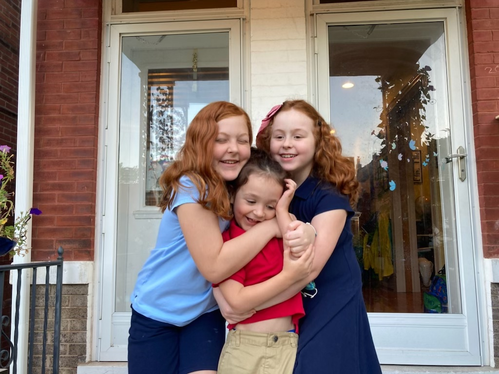 The Danieley siblings, Lucy, 10, Teddy, 5, and Ruby, 9, hug on their first day back to school on Sept. 7, 2021. // Courtesy Teresa Danieley