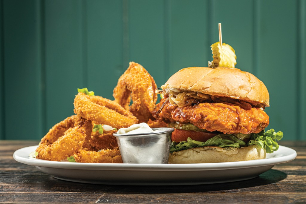 The fried chicken sandwich (buffalo style) with onion rings. // Photo by Zach Bauman